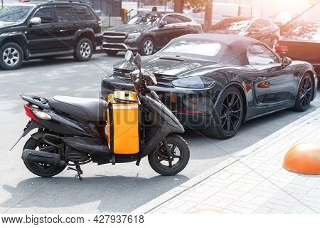 Fast Express Takeaway Online Gig Order Food Delivery Scooter With Red Orange Bag Box Parked At Traff