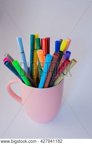 Pink Cup Full Of Colored Markers. White Background And Copy Space