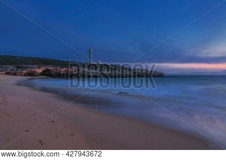 Lighthouse of Ponta do Altar under gloomy sunset sky. View from Pintadinho beach. Ferragudo, Lagoa, Algarve, Portugal