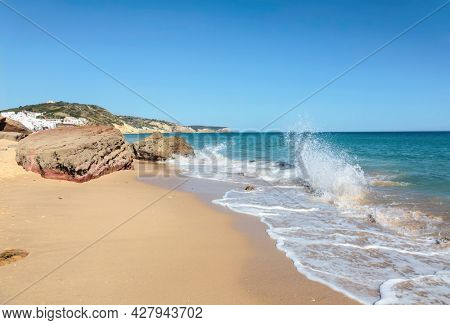 Atlantic coast with stones, sand and clear water. Salem beach, Algarve, Portugal