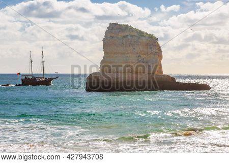 Pleasure tourist ship near the famous beach of Praia dos Caneiros. Algarve.Portugal