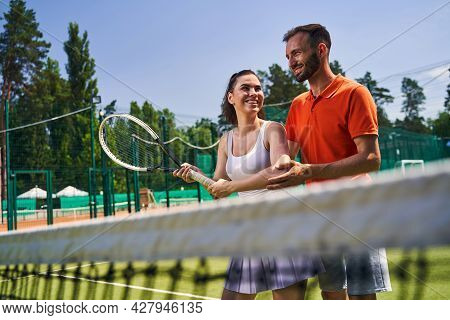 Woman Learning A Proper Serve Stance During The Tennis Session