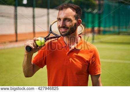 Joyous Male Player Standing On The Tennis Court