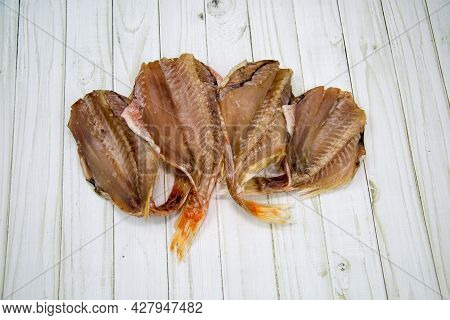 Sea Bass (latin Sebastes) Dried Without A Head Folded Like A Fan On A Wooden Table. Food Is A Delica