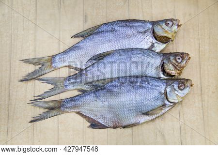 Bream (latin Abramis Brama) Dried With The Head Folded In A Row On A Wooden Table. Food Is A Delicac