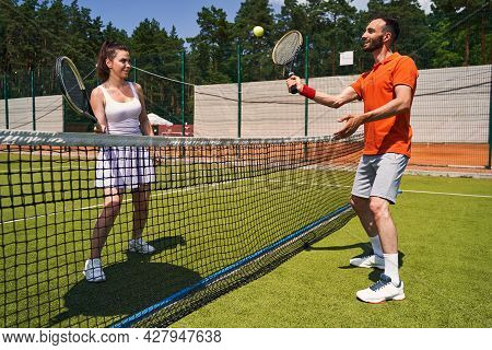 Joyous Cute Sportsman Serving The Ball To His Tennis Partner