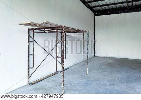 Provide Scaffolding For Interior Construction And Painting Of Warehouse Concrete Wall.empty White Ro
