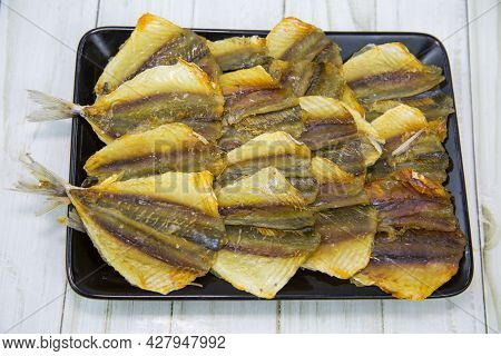 Yellow Tabby (latin: Selaroides Leptolepis) Dried Folded In Rows On A Black Rectangular Plate With A