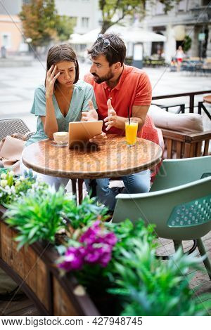 Young Couple Arguing In Cafe. People, Cheating, Conflict, Relationship Problems Concept.