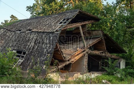 Ruins Of A House With A Collapsed Roof. The Remains Of The House Built Of Bricks And Wooden Planks.