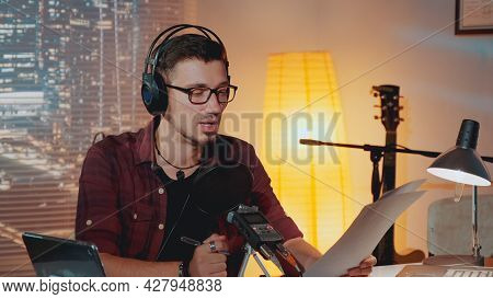 Radio News Anchorman Working In The Evening In Home Studio, Reading Something From A Piece Of Paper