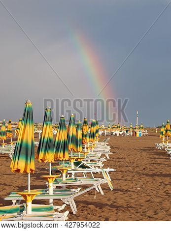 Colorful Rainbow Emerging From The Beach With Many Closed Sunshades After The Storm