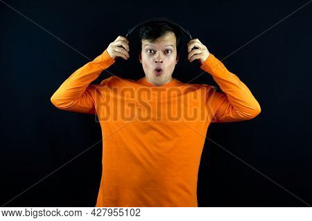 The Man Holds The Headphones And Looks Amazing. The Man Looks Scared Or Surprised. The Guy In The Or