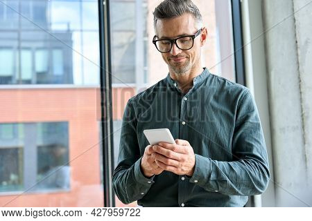 Smiling Mature Businessman Holding Smartphone Standing In Office. Middle Aged Manager Ceo Using Cell