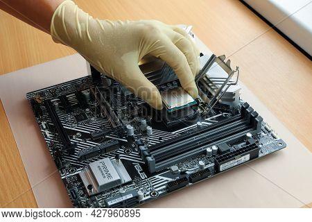 St. Petersburg, Russia - July 17, 2021: Gloved Hand Installs Latest Intel Processor I7 11700k Into M