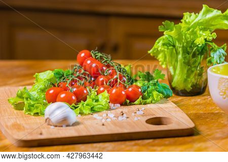 Fresh Cherry Tomatoes With Green Salad And Garlic On A Cutting Board.