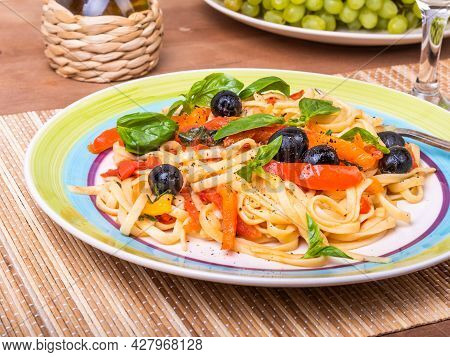 Classic Vegetarian Pasta - Linguini With Tomatoes, Peppers And Olives With Basil Leaves, Serving On