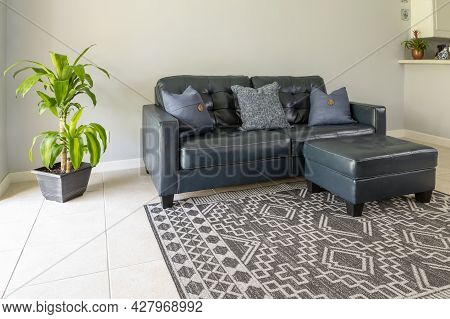 An Angled View Of A  Large Blue Moden Styled Love Seat And Ottoman Sofa Made Of Genuine Leather. The