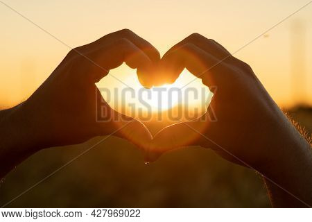 The Silhouette Of A Hand In The Shape Of A Love Heart At Sunset. Hands Forming A Heart Shape With Su