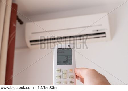 Close-up Of Man Hand Is Turn-on Air Conditioner Split Type By Remote Controller.