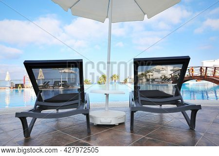Chaise Longues And Beach Parasol Near Outdoor Swimming Pool At Resort