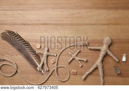 Voodoo Doll Pierced With Pins And Ceremonial Items On Wooden Table, Flat Lay. Space For Text