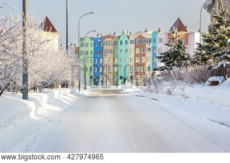 Snowy Street Leading To A Multi-colored Multi-storey Building