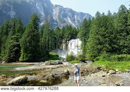 A Woman Standing On The Shores With A Waterfall, Forests And A Giant Rock Face Behind Her, On A Beau