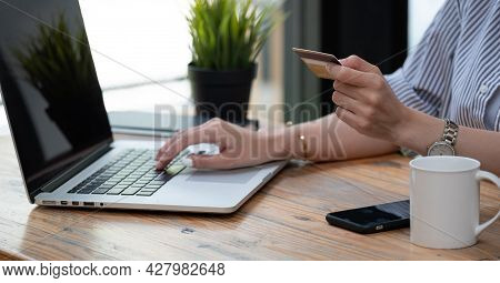Close Up Hand Of Asian Woman Buying Online With Laptop Computer And Credit Card At Home