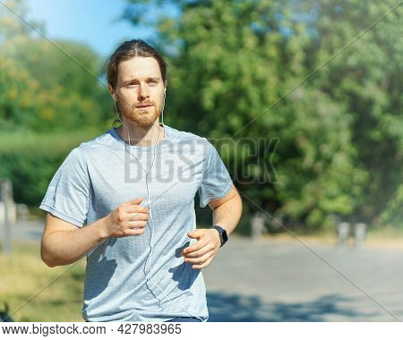 Young Athletic Handsome Man Running In Green Park Outdoors On Sunny Summer Day, Male Sportsman Dress
