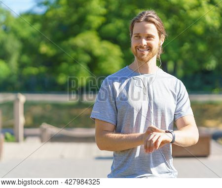 Positive Young Handsome Sportsman In Earphones Using Fitness Bracelet Or Smart Watch On Wrist And Lo