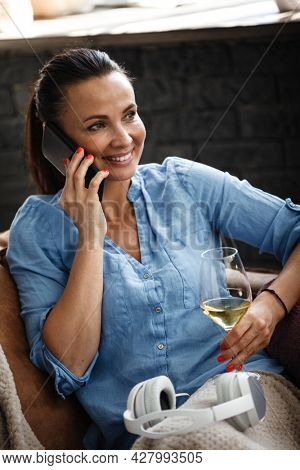 Leisure time concept. Happy beautiful woman talks on a phone and drinks white wine from glass sitting on a couch indoors. Female spending her free day and relaxing at home alone.