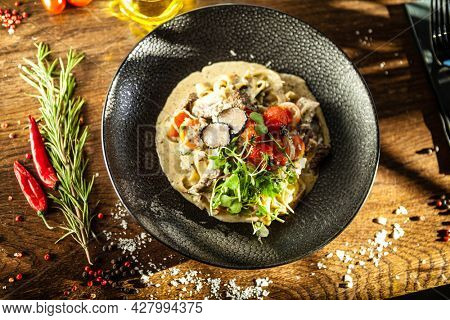 Black Angus beef tagliatelle pasta with fresh black truffles and parmegano. Delicious healthy traditional food closeup served for lunch in modern gourmet cuisine restaurant.