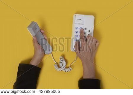 Someone Dials The Phone Number On White Wired Landline Telephone