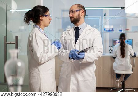 Scientists Coworkers Using Digital Tablet Working In Medical Research Laboratory, Analysing Biochemi