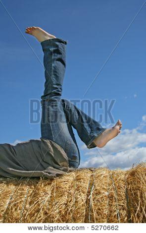 Feminine Legs On A Bale Of Straw