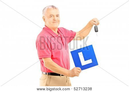 Smiling senior man holding a L plate and car key isolated on white background