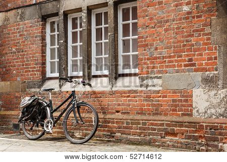 Retro bike against the brick wall of an old building with nobody. poster