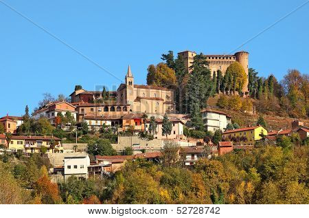 Small town and medieval castle among autumnal trees on top of the hill in Piedmont, Northern Italy.