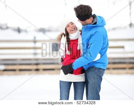 Ice skating romantic couple on date iceskating embracing. Young couple holding hands on ice skates outdoors on open air rink in snowy winter landscape. Multiracial couple, Asian woman, caucasian man