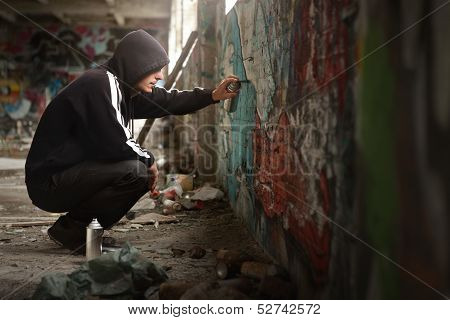 Illegal Young Man Spraying Paint On A Graffiti Wall.