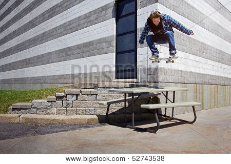 Young Skateboarder doing a Ollie trick over a Picnic Table poster