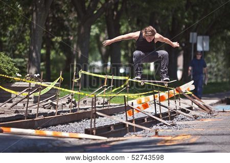Skateboarder Doing A Ollie Trick Over Construction