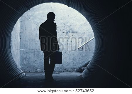 Businessman In Silhouette Walking In A Dark Tunnel
