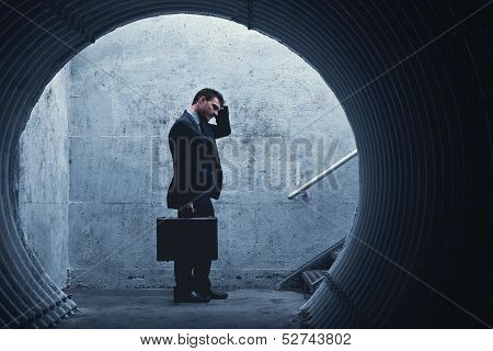 Desparate Businessman Holding His Head In A Dark Tunnel.