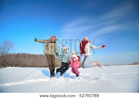 Happy parents and their kids in winterwear having fun outside
