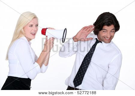 a blonde woman yelling on a man with a megaphone