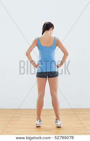 Full length rear view of a slim sporty young woman tip toeing