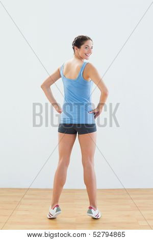 Rear view portrait of a smiling slim young woman tip toeing