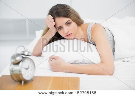 Serious young woman lying on her bed under the cover looking at camera